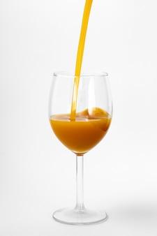 Suco de laranja fresco é servido em um copo em um fundo branco
