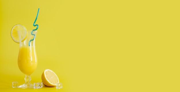 Suco de laranja fresco em copo, decorado com rodela de limão e canudo azul. coquetel de verão no fundo amarelo. molde colorido. espaço livre para texto, copie o espaço.