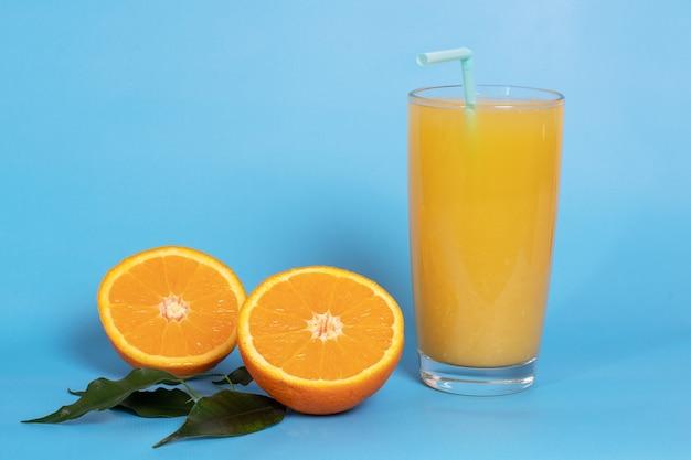 Suco de laranja fresco em um copo com frutas cortadas ao meio e fatiadas em folhas verdes isoladas em um azul