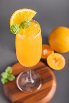 Suco de laranja fresco em vidro com hortelã, frutas frescas. foco seletivo.