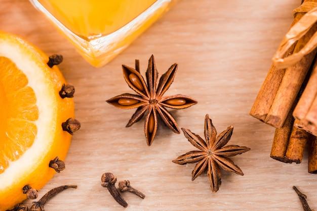 Suco de laranja fresco no frasco de vidro. especiarias de canela, cardamomo, cravo. em um fundo de madeira