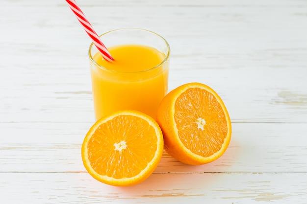 Suco de laranja fresco no fundo de madeira branco