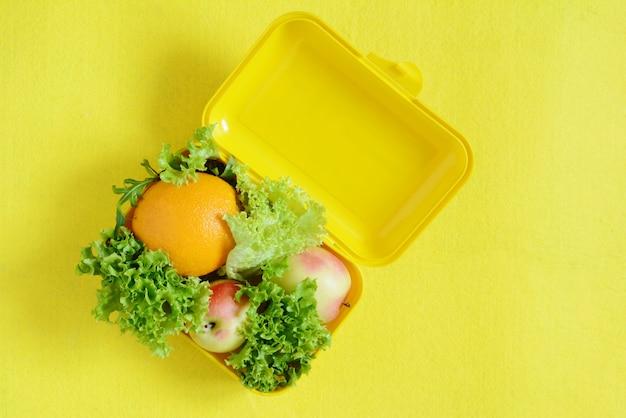 Suco de laranja maduro, maçãs e folhas de alface em um fundo amarelo