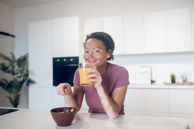 Suco de laranja. mulher jovem de pele escura segurando um copo com suco de laranja