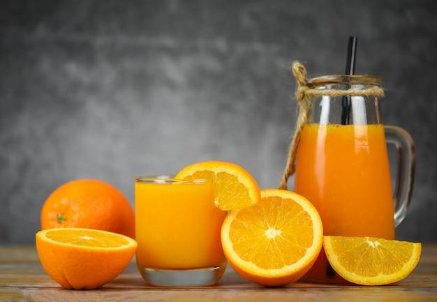 Suco de laranja na jarra de vidro e fatia de frutas frescas de laranja na mesa de madeira