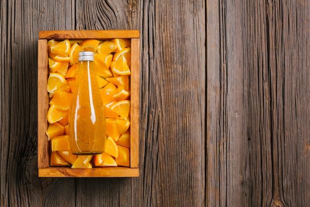 Suco de laranja no fundo de madeira copyspace