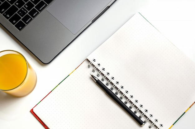 Suco de laranja no local de trabalho. portátil, vidro do suco de laranja e caderno na mesa branca.