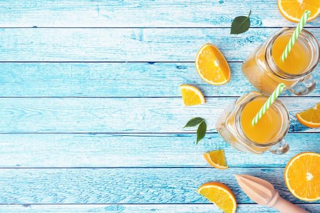 Suco de laranja nos frascos de vidro e laranjas frescas em um fundo azul.