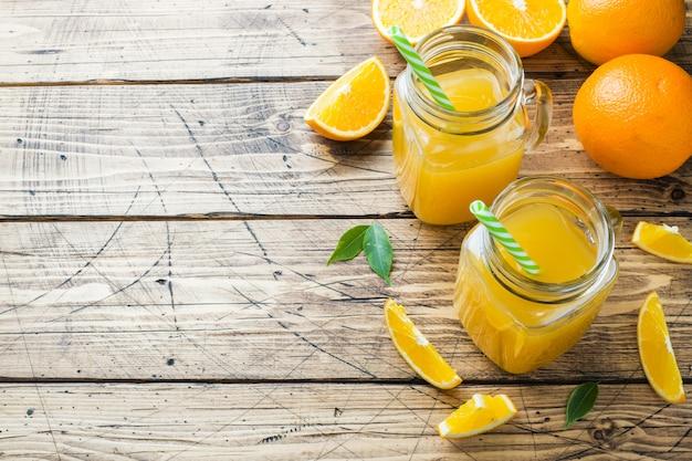 Suco de laranja nos frascos de vidro e laranjas frescas em um fundo rústico de madeira. copie o espaço.