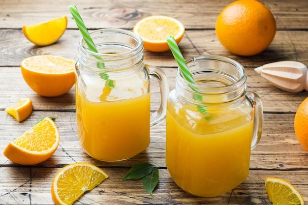 Suco de laranja nos frascos de vidro e laranjas frescas em um fundo rústico de madeira.