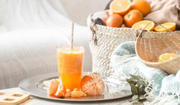 Suco de laranja orgânico fresco cultivado no interior da casa, com um cobertor turquesa e uma cesta de frutas