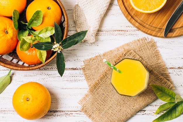 Suco de laranja refrescante ao lado do cesto cheio de laranjas
