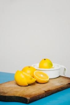 Suco de limão fatiado com espremedor manual na tábua de cortar