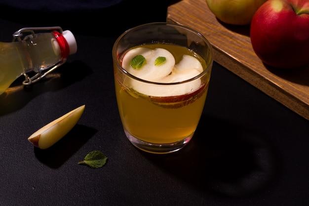 Suco de maçã caseiro em um copo ao lado de maçãs frescas.
