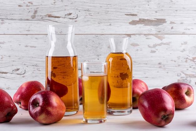 Suco de maçã com maçãs vermelhas na mesa de madeira branca