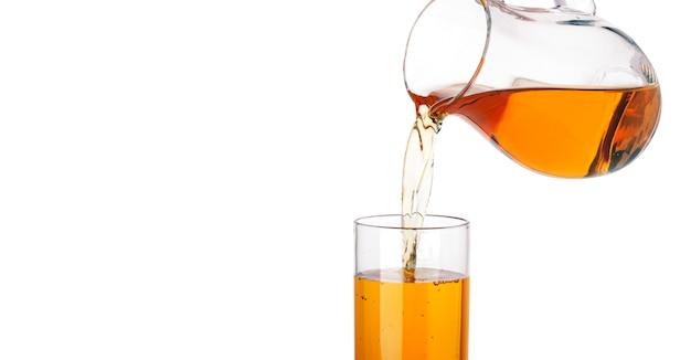 Suco de maçã derramando do jarro em vidro, isolado no branco