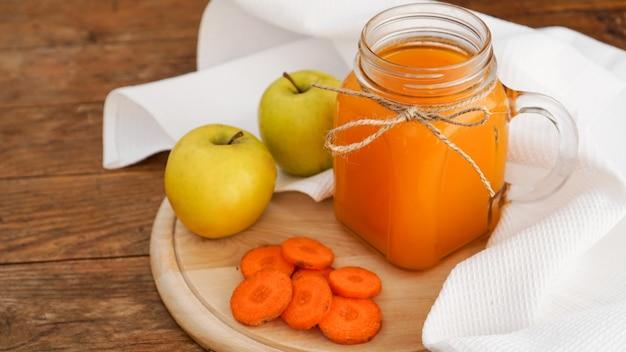Suco de maçã e cenoura em vidro, legumes frescos e frutas em fundo de madeira. estilo rústico. bebida caseira com vitaminas