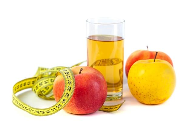 Suco de maçã e maçã com fita métrica em fundo branco, comida saudável