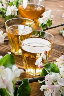 Suco de maçã em um copo de maçã entre flores