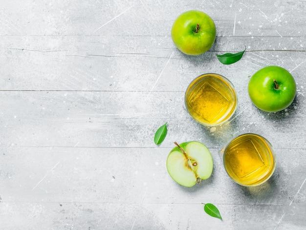 Suco de maçã em um copo de vidro com maçãs frescas.