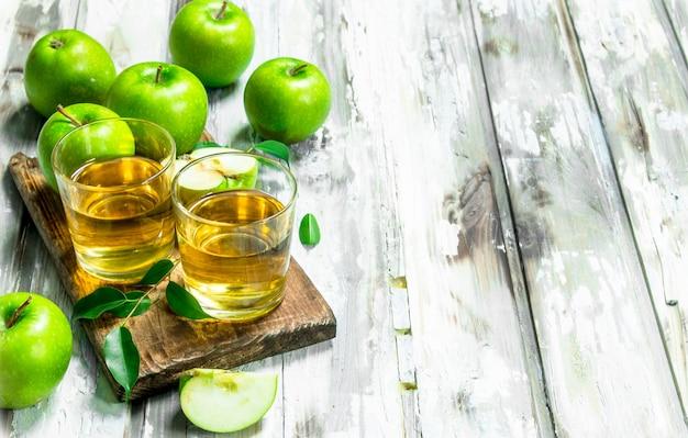 Suco de maçã em um copo de vidro em uma placa de madeira.