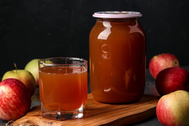 Suco de maçã em um copo e uma jarra, cozida em um espremedor, colhendo suco de uma colheita de maçã em fundo escuro
