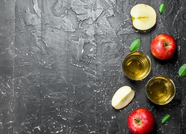 Suco de maçã em uma jarra de vidro com maçãs frescas em uma caixa. sobre um fundo escuro e rústico.