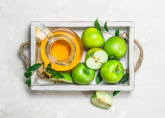 Suco de maçã em uma jarra de vidro com maçãs frescas.