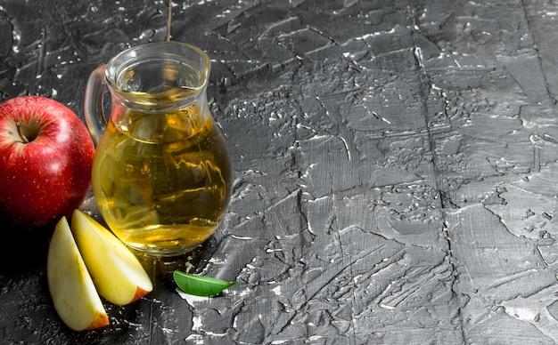 Suco de maçã em uma jarra de vidro com maçãs vermelhas frescas.