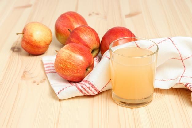 Suco de maçã espremido no copo com pano de prato e maçãs