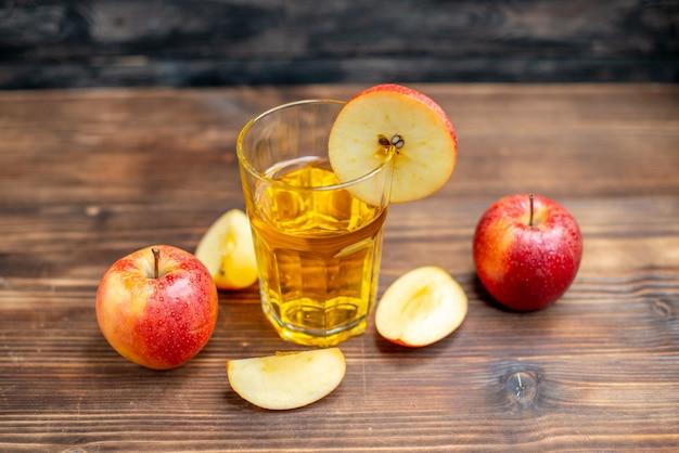 Suco de maçã fresco com maçãs frescas em uma mesa de madeira marrom. foto colorida suco de maçã