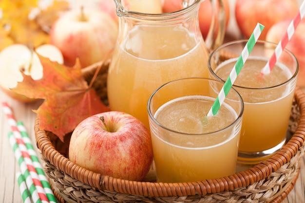 Suco de maçã fresco e maçãs na cesta