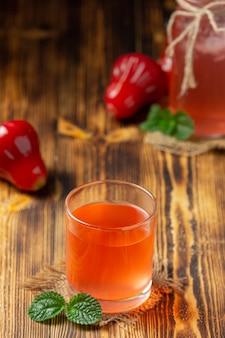 Suco de maçã rosa em superfície de madeira escura