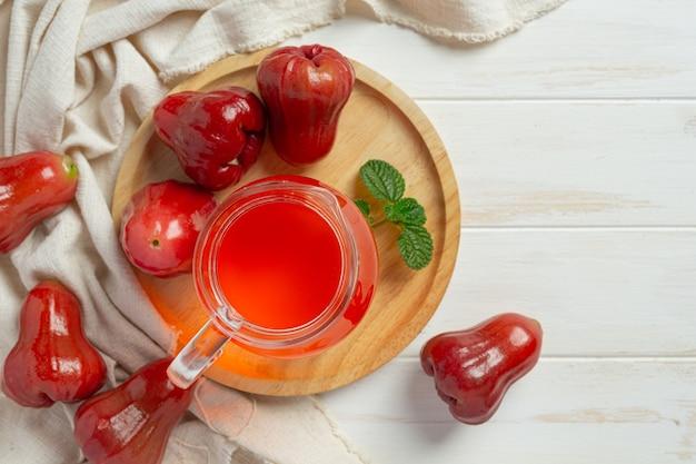 Suco de maçã rosa na superfície de madeira branca