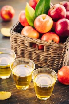 Suco de maçãs em vidro com maçã no cesto