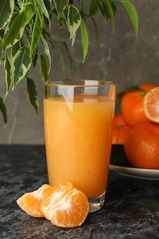 Suco de mandarim e ingredientes na mesa preta esfumada