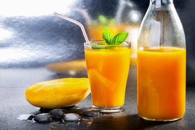 Suco de manga de smoothie de frutas tropicais frescas e manga fresca.