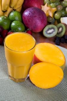 Suco de manga fresco com frutas no fundo.