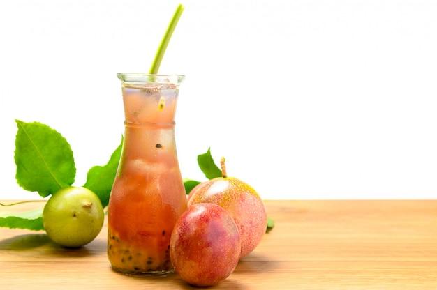 Suco de maracujá em vidro com frutas na mesa de madeira