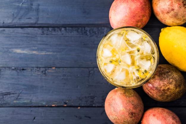 Suco de maracujá fresco e saudável com maracujá e limão no fundo.