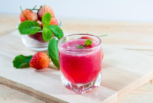 Suco de morangos frescos em vidro transparente para beber na madeira
