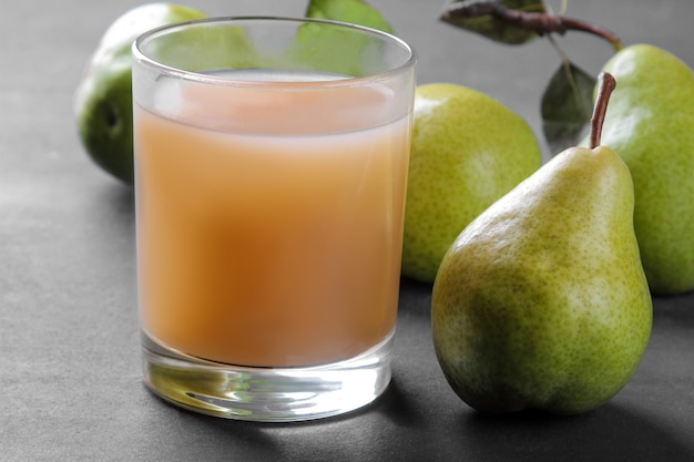 Suco de pêra em um copo e peras frescas maduras em uma mesa preta. fechar-se