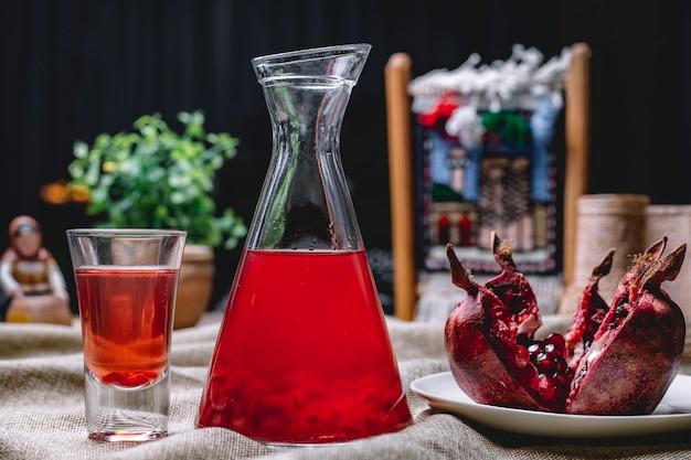 Suco de pomegrante no jarro com as sementes dentro da fruta tiro vista lateral