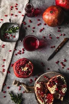 Suco de romã vermelha em um copo, romã madura e cortada e um raminho de hortelã sobre um fundo cinza de concreto. conceito de vitamina, antioxidantes e alimentos saudáveis. camada plana. vista superior.