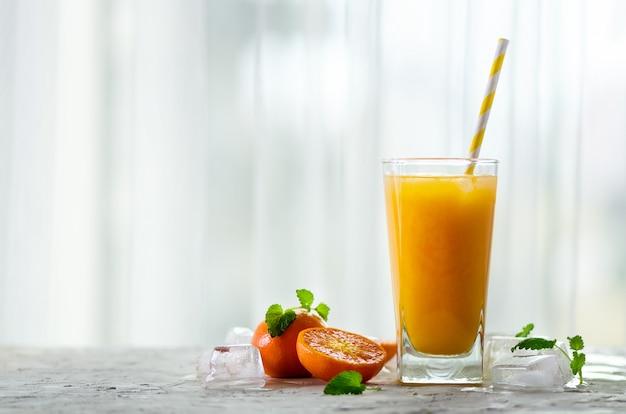 Suco de tangerina fresco em vidro. frutas laranja com gelo, hortelã. bebida fria para o dia quente de verão. copyspace