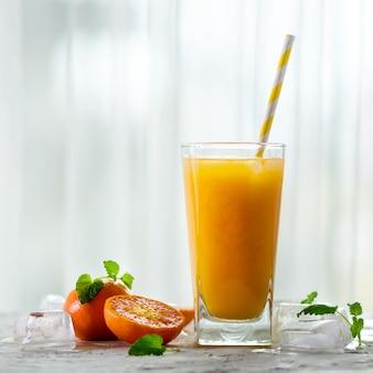 Suco de tangerina fresco em vidro. frutas laranja com gelo, hortelã. bebida fria para o dia quente de verão.
