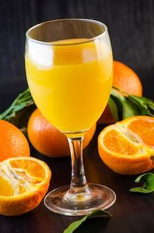 Suco de tangerina natural orgânico fresco em um copo em um fundo escuro