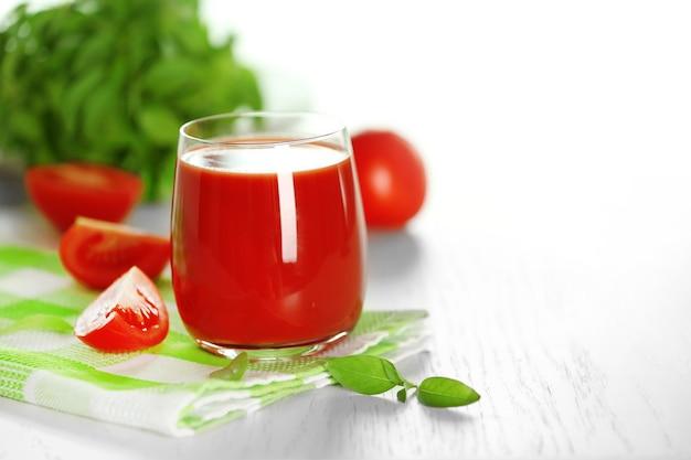 Suco de tomate e tomate fresco em close-up de mesa de madeira