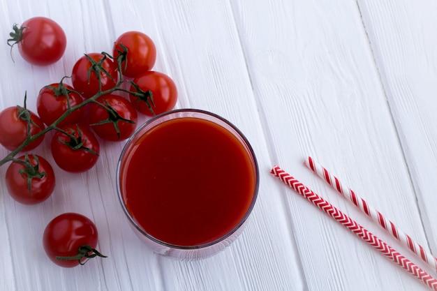 Suco de tomate e tomate na superfície de madeira branca. vista superior.