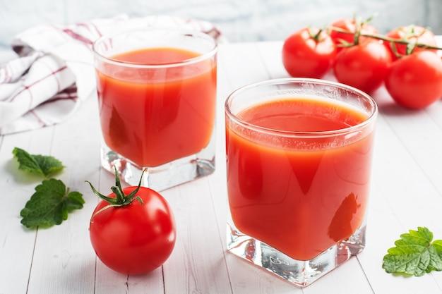 Suco de tomate em copos de vidro e tomates frescos maduros em um galho.